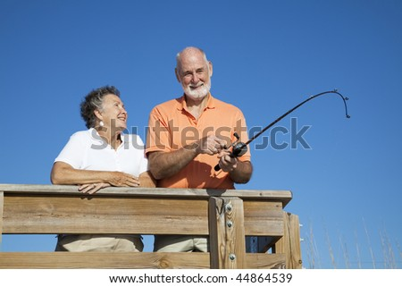 Senior couple on vacation, enjoying fishing from a pier.