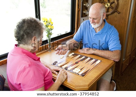 Senior couple on vacation playing backgammon in their motor home.  Motion blur on the man's hand as he shakes the dice.