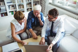Senior couple planning their investments with financial advisor in living room