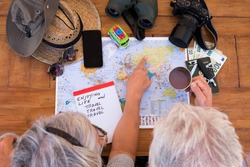 Senior couple planning travel around the world - active elderly vacation, free retirement concept. Wooden table with camera, mobile phone, money