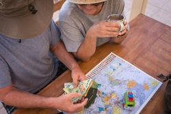 Senior couple planning travel around the world - active elderly vacation, free retirement concept. Wooden table with map, passport and money