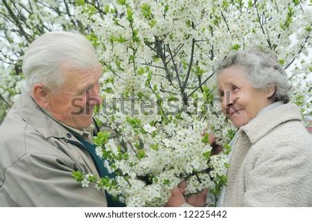 senior couple play hide-and-seek among flowering garden