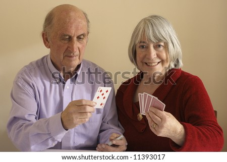 Senior couple playing cards enjoying retirement.