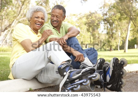Senior Couple Putting On In Line Skates In Park