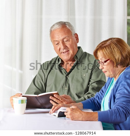 Senior couple reading books together in a rest home