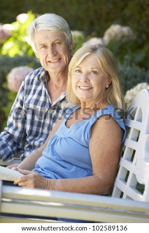 Senior couple reading in garden