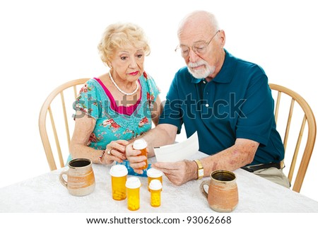 Senior couple reading instructions from the pharmacy on how to take their medication. White background.