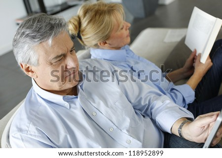 Senior couple relaxing at home in sofa