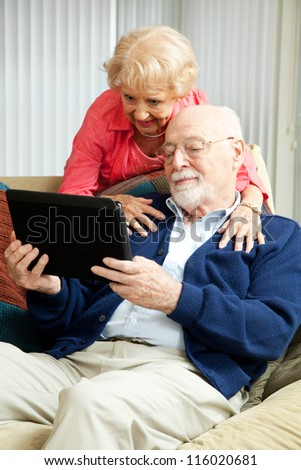 Senior couple relaxing at home, using their tablet PC.