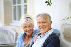 Senior couple relaxing on bench by the house