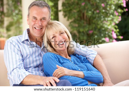 Senior Couple Relaxing On Sofa At Home - stock photo