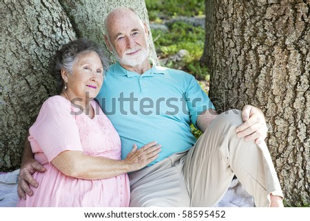 Senior couple relaxing together in the park under a tree.