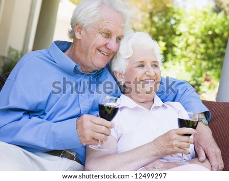Senior couple relaxing with glass of red wine