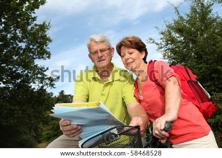 Senior couple riding bicycle in countryside with map