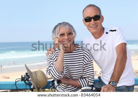 Senior couple riding bikes by the beach