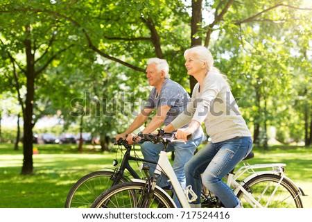 Senior Couple Riding Bikes In Park