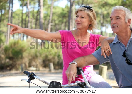 senior couple riding bikes in the park