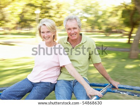 Senior Couple Riding On Roundabout In Park