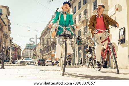 Senior couple riding their bicycle in the city center. Mature people making urban healthy lifestyle