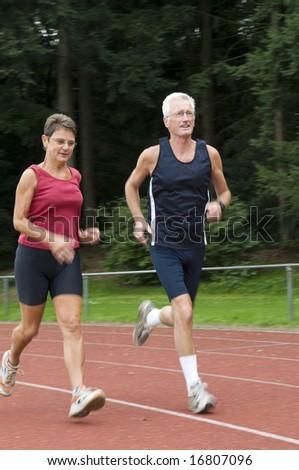senior couple running on a race track