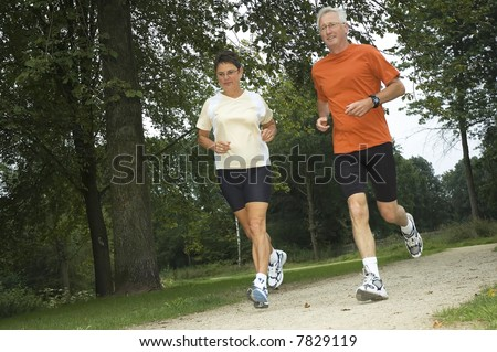 Senior couple running through the woods