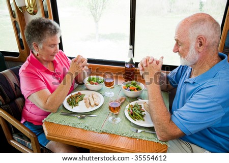 Senior couple say grace before eating a meal in their motor home.