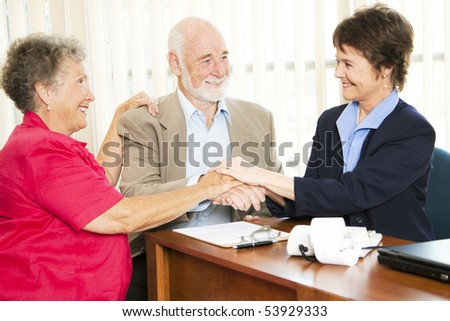 Senior couple shakes hands with their financial advisor or broker.
