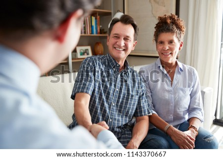 Senior Couple Shaking Hands With Male Financial Advisor At Home #1143370667