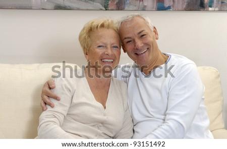 Senior couple sharing and smiling at home.