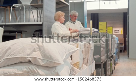 Senior couple shopping for new comfortable sleep pillows at furnishings store #1502468573