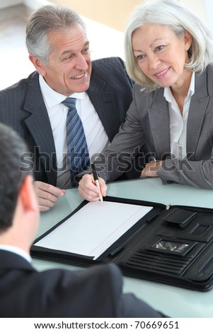 Senior couple signing home purchase contract