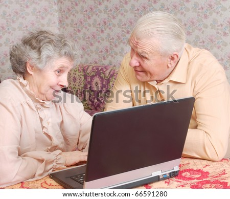 senior couple sit ar the laptop and discuss