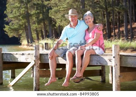 Senior couple sitting by lake