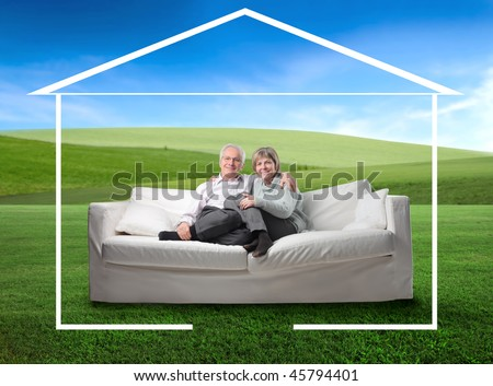 Senior couple sitting in a couch and surrounded by the form of a house