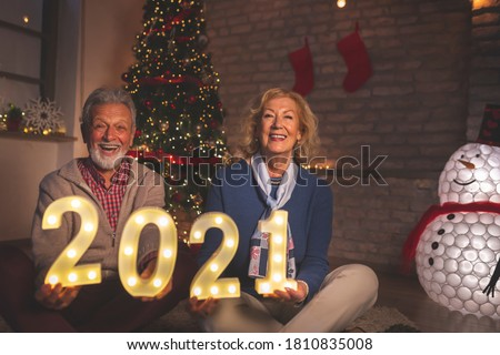 Senior couple sitting in front of nicely decorated Christmas tree, holding illuminating numbers 2021, respresenting the upcoming New Year