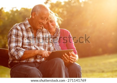 Senior couple sitting on a park bench on sunny autumn day with tablet and relaxing.