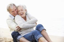 Senior Couple Sitting On Beach Together