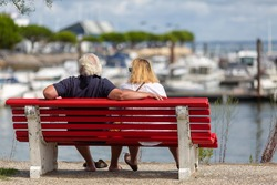 senior couple sitting on bench watching boats