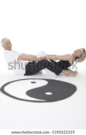 Senior couple sitting on floor next to yin yang symbol