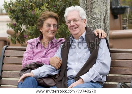 Senior Couple Sitting On Park Bench Outdoor