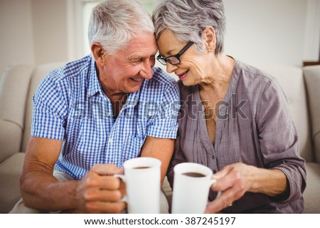 Senior couple sitting on sofa and having coffee in living room