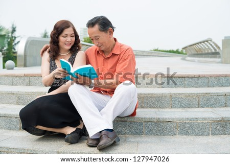 Senior couple sitting outdoors and reading