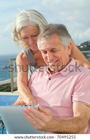Senior couple sitting outside with electronic tablet