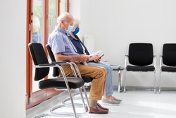 Senior couple sitting with face masks in a bright waiting room of  a hospital or an office - the man is reading a test result - the woman looks at a smart phone