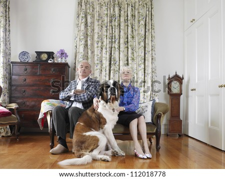 Senior couple sitting with their dog