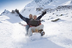 Senior couple sledding in mountains on winter day