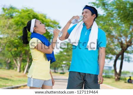 Senior couple standing and drinking water