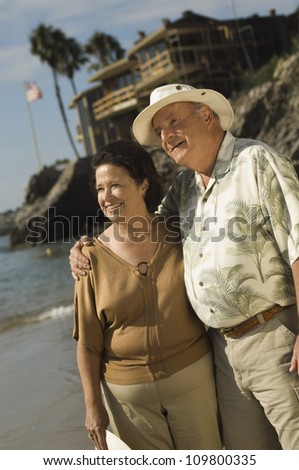 Senior couple standing at beach and looking away