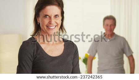 Senior couple standing in living room smiling