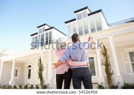 Senior Couple Standing Outside Dream Home